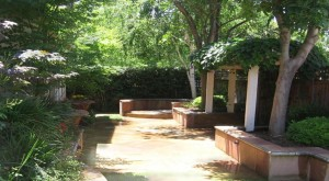 Sandstone patios, walkways and walls meander through the yard, with trellises at one end and the middle