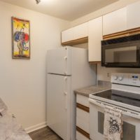 Kitchen with fridge, microwave, oven / stove, new slab granite counters and engineered hardwood flooring.
