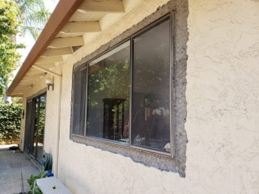 Image of stucco chipped away from window before replacement - what needs updating in an older home may include single pane windows